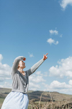 Shelley Richmond RETRO WOMAN IN COUNTRYSIDE POINTING AT SKY