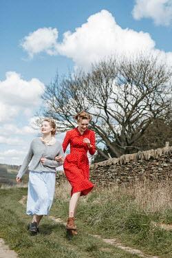 Shelley Richmond TWO RETRO WOMEN RUNNING IN COUNTRY LANE