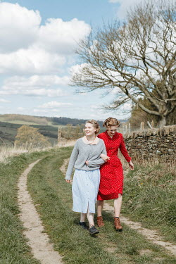 Shelley Richmond TWO RETRO WOMEN ARM IN ARM ON COUNTRY LANE