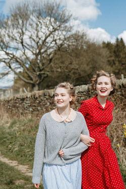 Shelley Richmond TWO HAPPY RETRO WOMEN ARM IN ARM IN COUNTRYSIDE