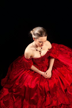 Miguel Sobreira BLONDE WOMAN SITTING IN RED GOWN AND NECKLACE