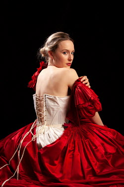 Miguel Sobreira BLONDE WOMAN SITTING IN CORSET AND RED DRESS