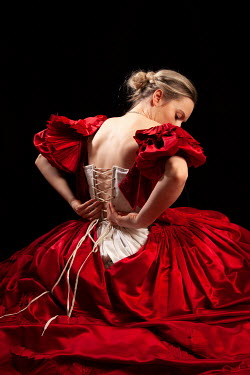 Miguel Sobreira BLONDE WOMAN SITTING RED DRESS UNTYING CORSET