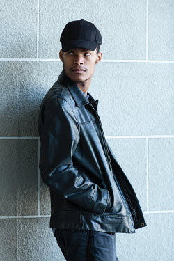 Magdalena Russocka young modern man wearing leather jacket and baseball cap leaning against wall