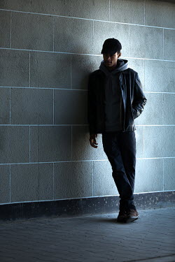 Magdalena Russocka young modern man wearing leather jacket, hoodie and baseball cap leaning against wall