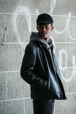 Magdalena Russocka young modern man wearing leather jacket, hoodie and baseball cap standing by wall