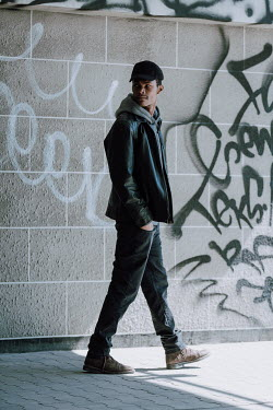 Magdalena Russocka young modern man wearing leather jacket, hoodie and baseball cap walking by wall