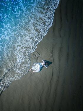 Mary Wethey WOMAN IN WHITE DRESS LYING ON SANDY BEACH