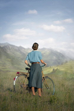 Ildiko Neer Vintage woman with bicycle by mountains