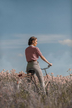 Ildiko Neer Vintage woman sitting on bike in meadow