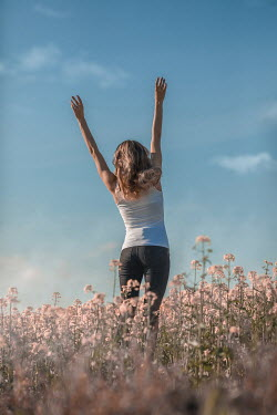 Ildiko Neer HAPPY WOMAN JUMPING IN MEADOW OF FLOWERS