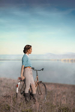 Ildiko Neer Land girl leaning on bicycle by lake