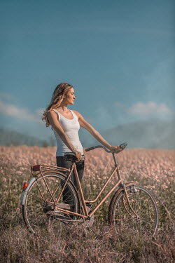 Ildiko Neer Young woman with bicycle at meadow