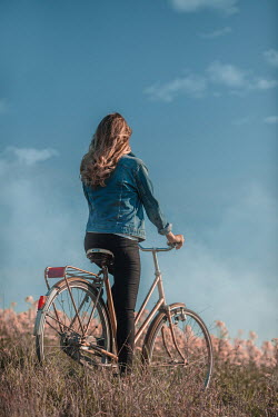 Ildiko Neer Young woman on bicycle at meadow