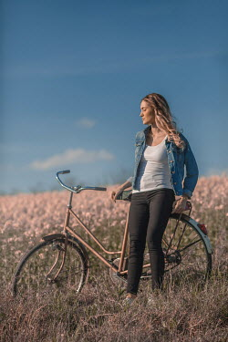 Ildiko Neer Young woman leaning on a bicycle
