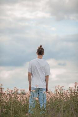 Ildiko Neer Young man standing in meadow