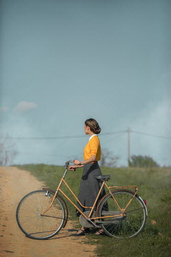 Ildiko Neer Vintage woman with bicycle by country road