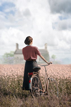 Ildiko Neer Vintage woman with bicycle standing in meadow by house