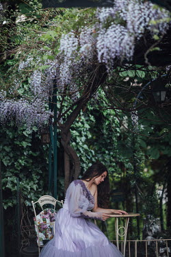 Jovana Rikalo WOMAN SITTING BY GARDEN TABLE WITH WISTERIA