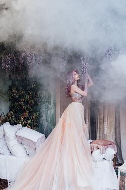 Jovana Rikalo WOMAN IN BEDROOM WITH PURPLE FLOWERS
