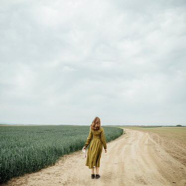 Jovana Rikalo WOMAN HOLDING LETTER STANDING IN FIELD