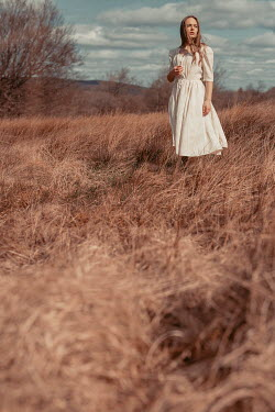 Shelley Richmond BRUNETTE GIRL WITH WHITE DRESS STANDING IN FIELD