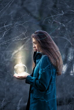 Tijana Moraca GIRL IN FOREST HOLDING GLOWING GLASS BALL