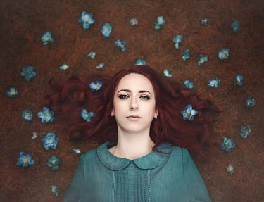 Anna Buczek WOMAN WITH RED HAIR LYING WITH BLUE FLOWERS