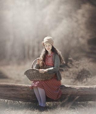 Anna Buczek GIRL SITTING ON LOG WITH BASKET