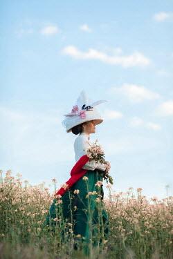 Ildiko Neer Historical woman holding bouquet of flowers in meadow