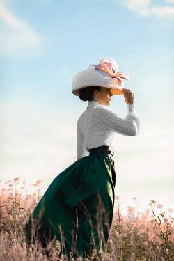 Ildiko Neer Historical woman holding hat in meadow