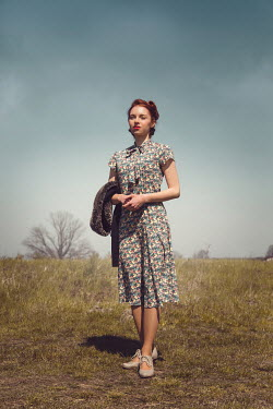 Joanna Czogala RETRO WOMAN IN PATTERNED DRESS OUTDOORS