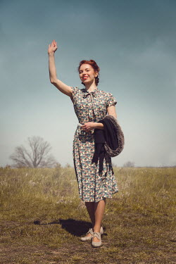 Joanna Czogala HAPPY RETRO WOMAN WAVING IN COUNTRYSIDE