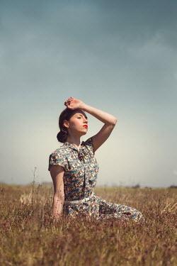 Joanna Czogala RETRO WOMAN IN PATTERNED DRESS SITTING OUTDOORS