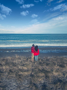 Mary Wethey COUPLE STANDING ON BEACH HUGGING