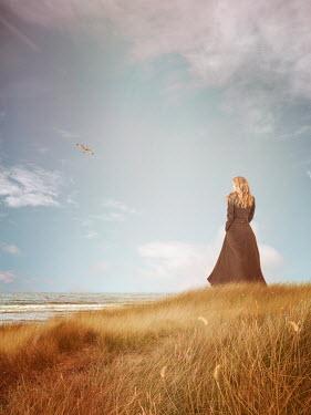Victoria Davies BLONDE WOMAN IN COAT ON DUNES WATCHING SEA
