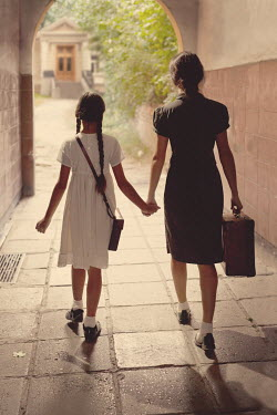 Kerstin Marinov MOTHER AND DAUGHTER HAND IN HAND WITH SUITCASE