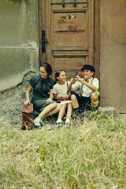 Kerstin Marinov HAPPY RETRO FAMILY SITTING OUTSIDE HOUSE