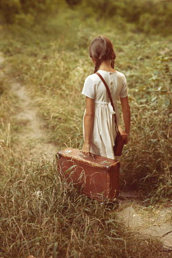 Kerstin Marinov LITTLE GIRL CARRYING SUITCASE ON COUNTRY PATH