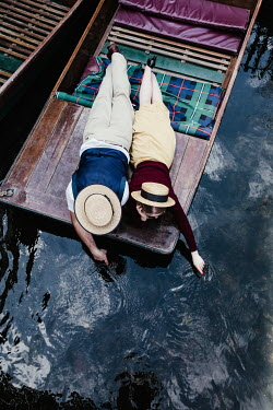 Matilda Delves RETRO COUPLE LYING ON PUNT DIPPING FINGERS