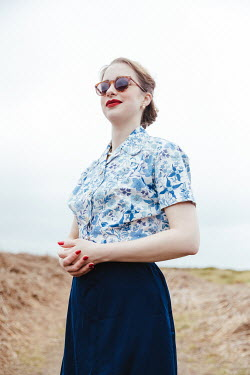 Matilda Delves RETRO WOMAN WITH SUNGLASSES STANDING IN COUNTRYSIDE