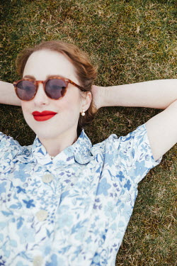 Matilda Delves RETRO WOMAN WITH SUNGLASSES LYING ON GRASS