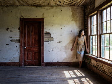 Rodney Harvey WOMAN STANDING BY WINDOW OF ABANDONED HOUSE