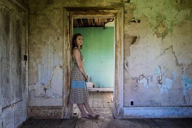 Rodney Harvey WOMAN STANDING IN DOORWAY OF DERELICT HOUSE
