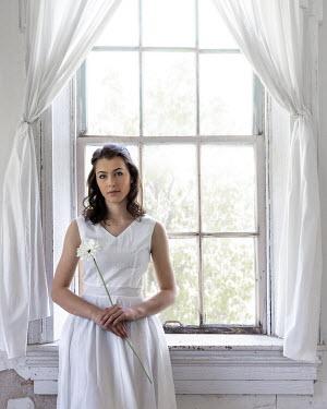 Rodney Harvey WOMAN IN WHITE BY WINDOW WITH FLOWER