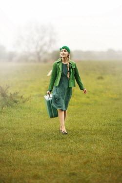 Anna Buczek GIRL IN GREEN WITH SUITCASE WALKING IN FIELD
