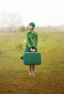 Anna Buczek BLONDE GIRL IN GREEN WITH SUITCASE IN COUNTRYSIDE