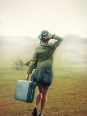Anna Buczek GIRL IN GREEN CARRYING SUITCASE IN COUNTRYSIDE