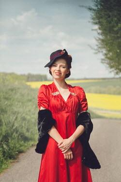 Joanna Czogala HAPPY RETRO WOMAN STANDING ON COUNTRY ROAD