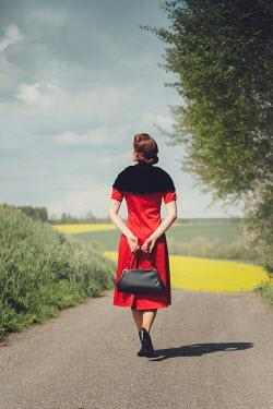 Joanna Czogala RETRO WOMAN WALKING ON COUNTRY ROAD
